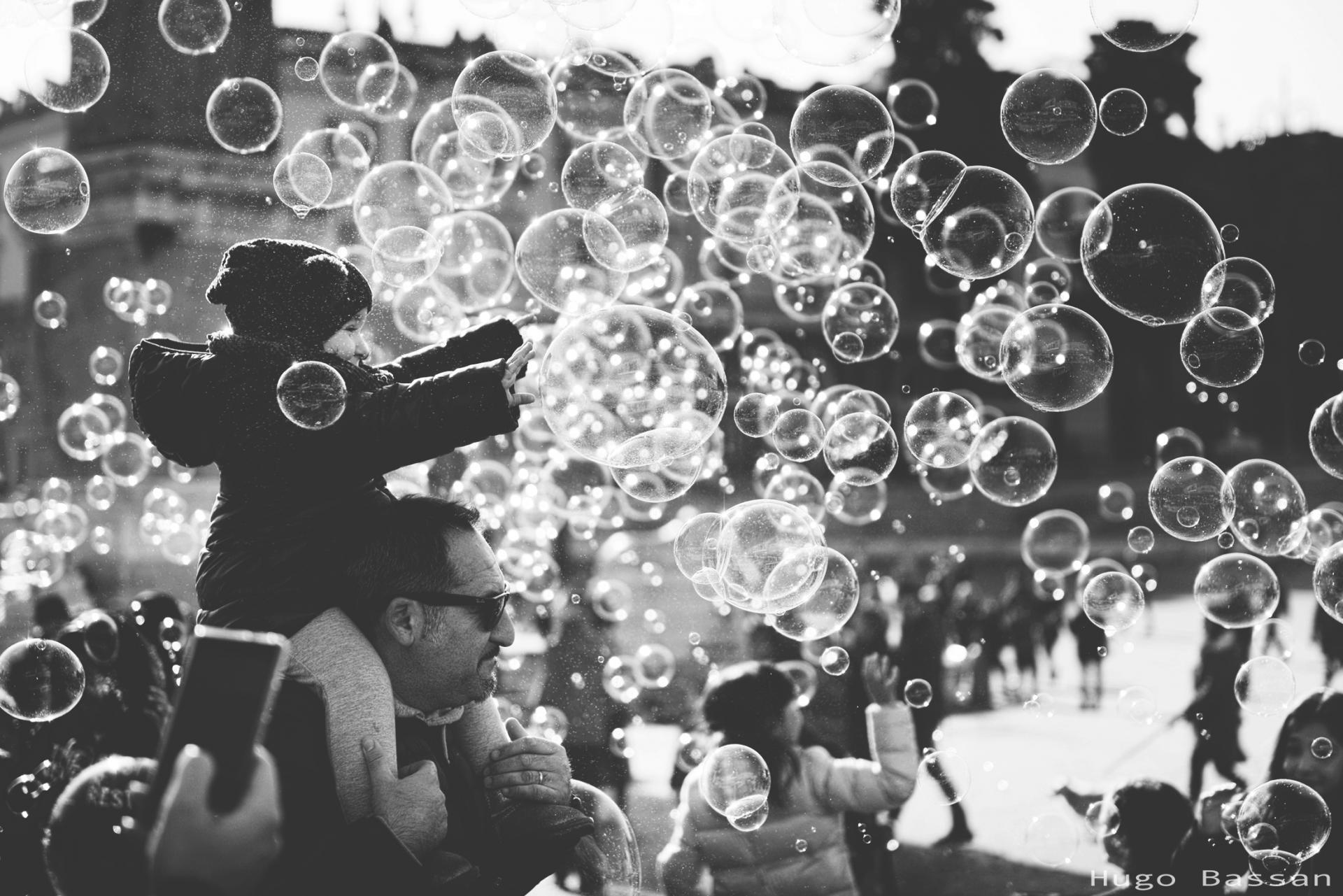 Fillette jouant avec les bulles d'un artiste de rue